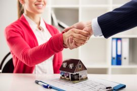 image of a woman in red sweater shaking hands on a real estate deal. There is a small model house on the table in front of her.